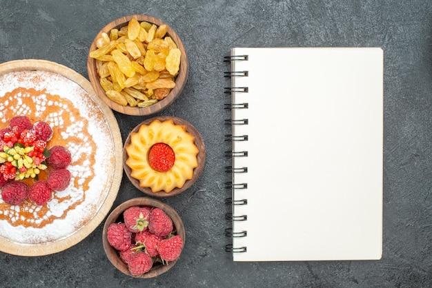 Bovenaanzicht lekkere frambozencake met rozijnen op grijs oppervlak suikerkoekjes thee zoete taartcake