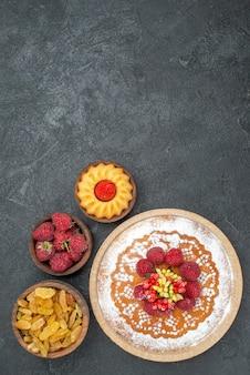 Bovenaanzicht lekkere frambozencake met rozijnen op grijze oppervlakte taart thee biscuit cake cookie sweet