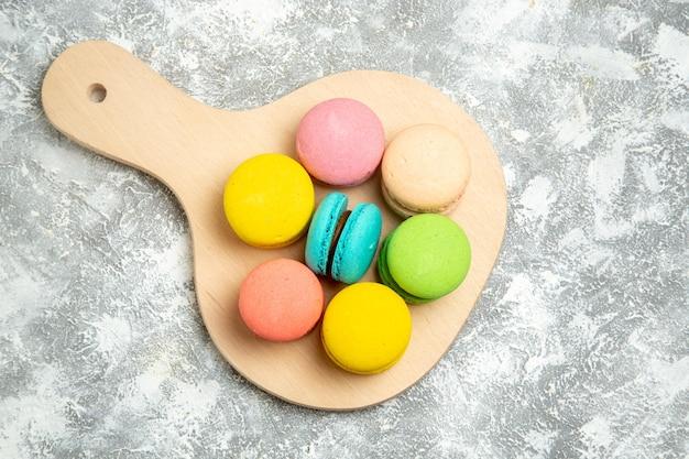 Bovenaanzicht lekkere franse macarons kleurrijke taarten op witte ondergrond