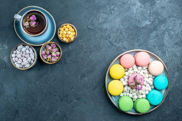 Bovenaanzicht lekkere franse macarons met kopje thee op donker