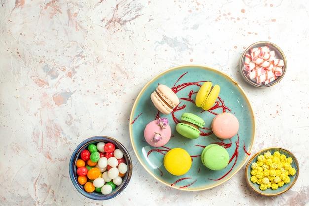 Bovenaanzicht lekkere franse macarons met snoepjes op witte zoete cake biscuit