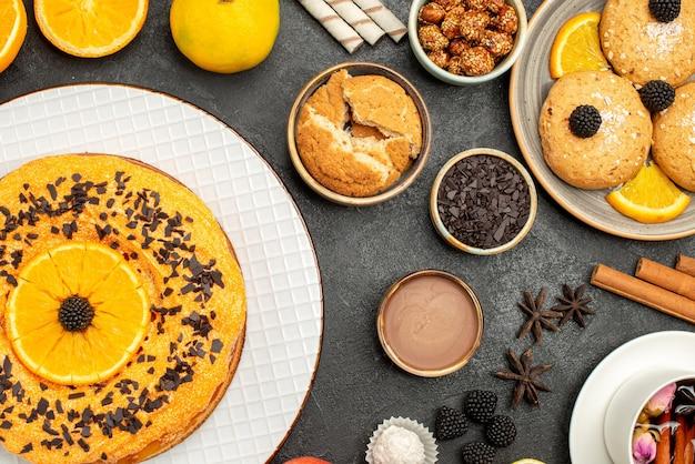 Bovenaanzicht lekkere fruitige cake met koekjes en kopje thee op een donkere ondergrond, koekjeskoekjesthee, zoete caketaart