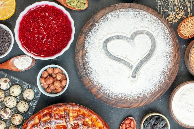 Bovenaanzicht lekkere fruitige taart met bloem jam en noten op de donkere fruit zoete taart suiker thee gebak dessert biscuit cake
