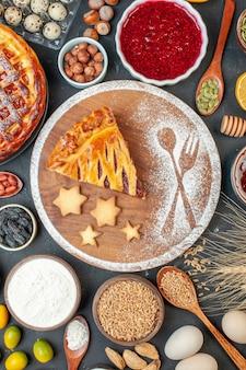 Bovenaanzicht lekkere fruittaart met jam, noten en bloem op de donkere biscuit dessert taart thee taart deeg zoete bak suiker