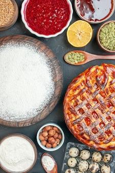 Bovenaanzicht lekkere fruittaart met jamnoten en bloem op de donkere desserttaart zoete thee cake deeg biscuit bak suiker