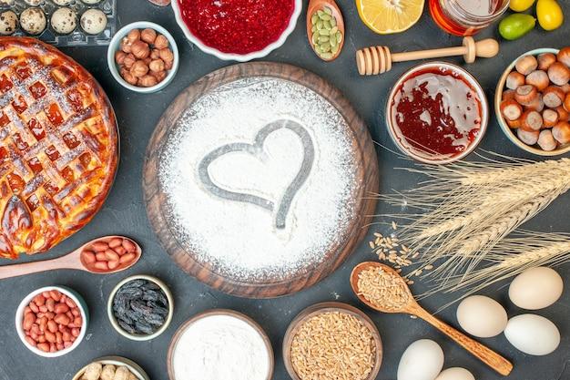 Bovenaanzicht lekkere fruittaart met jamnoten en bloem op donkere koekjesdesserttaart, zoete thee, cakedeeg, baksuiker