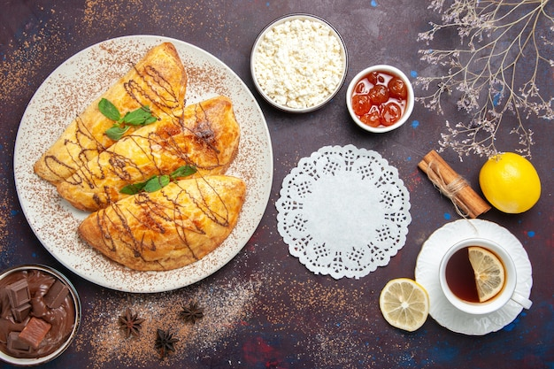 Bovenaanzicht lekkere gebakjes met kopje thee en kwark op donkere achtergrond gebak zoete bak theecake suikerkoekje