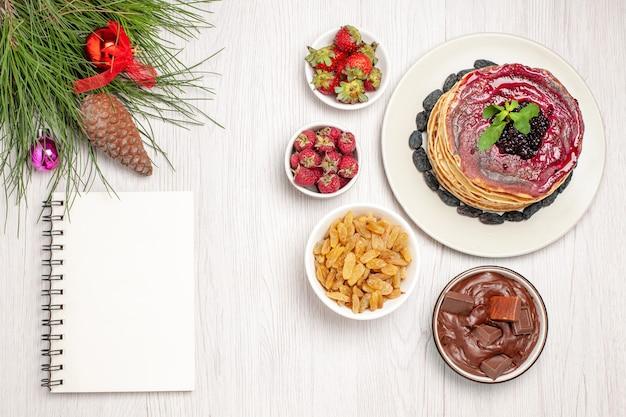 Bovenaanzicht lekkere geleipannenkoekjes met rozijnen en fruit op wit