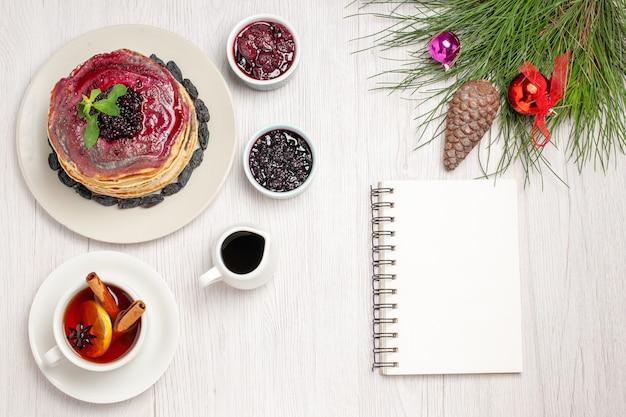 Bovenaanzicht lekkere geleipannenkoekjes met rozijnen fruitige gelei en kopje thee op wit