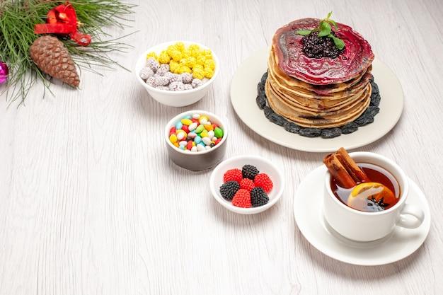 Bovenaanzicht lekkere geleipannenkoekjes met snoepjes en kopje thee op wit