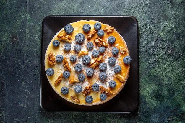 Bovenaanzicht lekkere honingcake met bosbessen en walnoten in plaat donker oppervlak