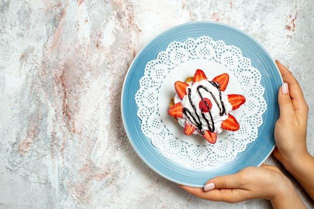 Bovenaanzicht lekkere kleine cake met room en aardbeien op wit