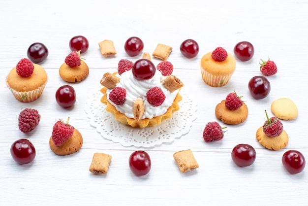 Bovenaanzicht lekkere kleine cakes met frambozen en room samen met koekjes en cakes op de lichte tafel cake biscuit zoete bessen fruit