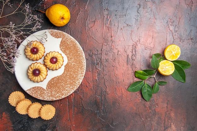 Bovenaanzicht lekkere kleine koekjes met fruit op donkere tafel cake zoete koekjessuiker