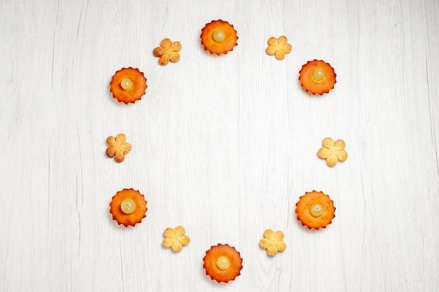 Bovenaanzicht lekkere kleine taarten bekleed met koekjes op wit bureau dessert biscuit thee taart taart zoete cookie