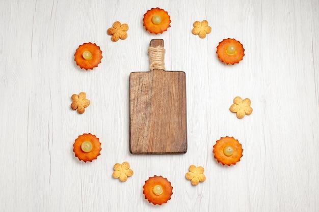Bovenaanzicht lekkere kleine taarten bekleed met koekjes op witte oppervlakte dessert biscuit thee taart taart zoete koekjes