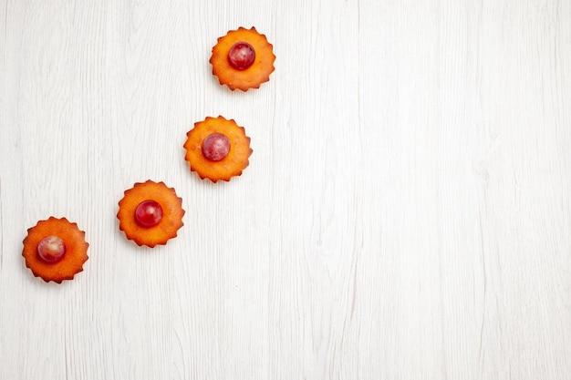 Bovenaanzicht lekkere kleine taarten bekleed op witte oppervlakte dessert cookie biscuit thee taart taart