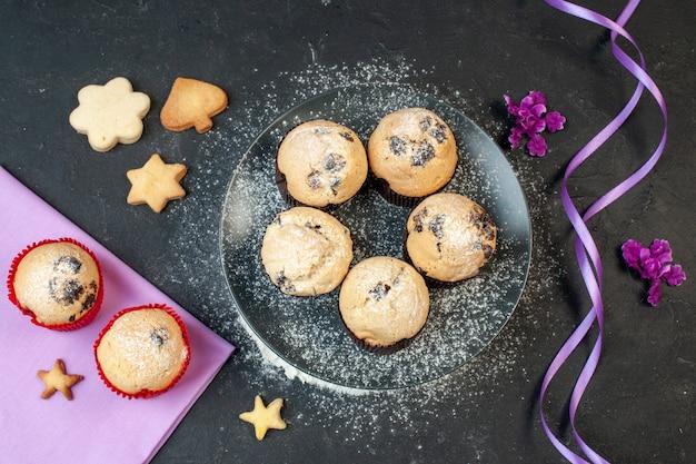 Bovenaanzicht lekkere kleine taarten met chocolade op donkere achtergrond