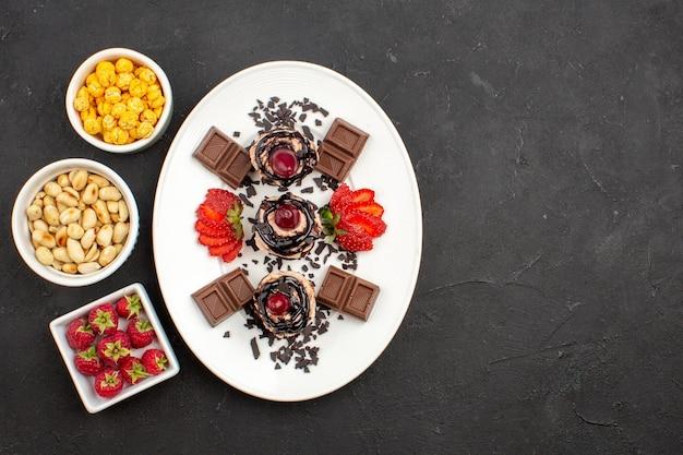 Bovenaanzicht lekkere kleine taarten met chocoladerepen en noten op donkere oppervlakte noten fruit cake taart cookie berry