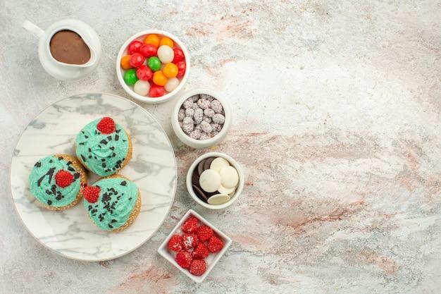 Bovenaanzicht lekkere kleine taarten met kleurrijke snoepjes en koekjes op witte oppervlakte dessert taart taart regenboog kleur snoep