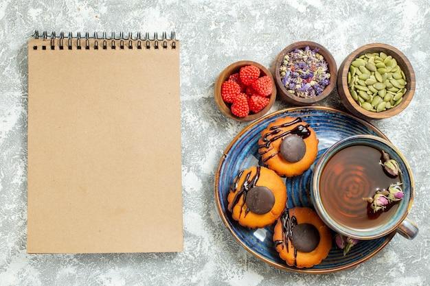 Bovenaanzicht lekkere kleine taarten met kopje thee op lichte witte vloer cake biscuit cookie dessert thee zoet