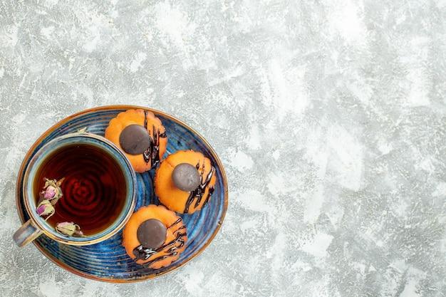 Bovenaanzicht lekkere kleine taarten met kopje thee op wit oppervlak cake biscuit cookie dessert thee zoet