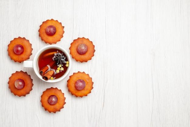 Bovenaanzicht lekkere kleine taarten met kopje thee op witte ondergrond dessert biscuit thee cake taart cookie