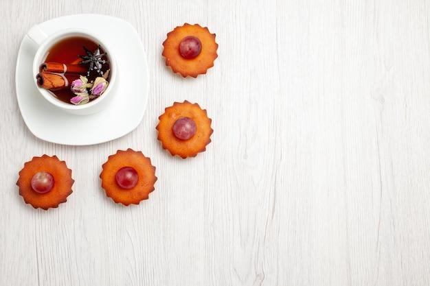 Bovenaanzicht lekkere kleine taarten met kopje thee op witte ondergrond dessert cookie biscuit thee taart taart