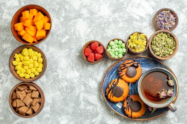 Bovenaanzicht lekkere kleine taarten met snoep en kopje thee op witte oppervlakte cake biscuit cookie dessert zoete thee