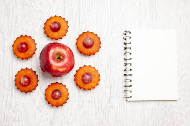 Bovenaanzicht lekkere kleine taarten met verse appel op witte oppervlakte dessert biscuit thee cake taart koekjes