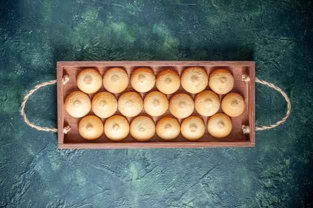 Bovenaanzicht lekkere koekjes in houten kist op donkerblauwe achtergrond suikerkoekje biscuit cake taart kleur zoete noten thee
