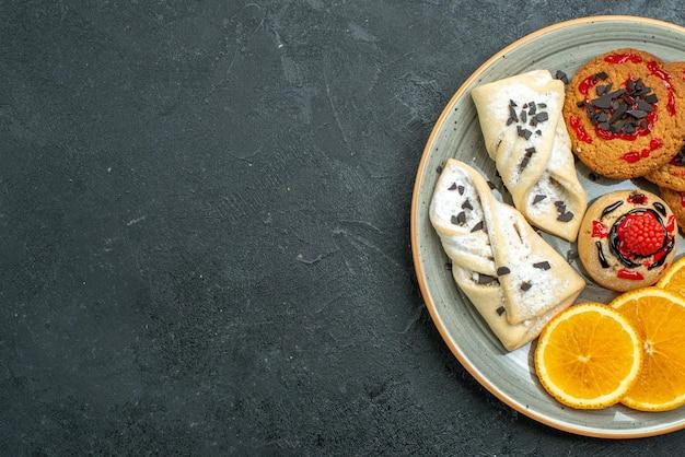 Bovenaanzicht lekkere koekjes met fruitige gebakjes en stukjes sinaasappel op donkere achtergrond fruit zoete cake taart thee suiker