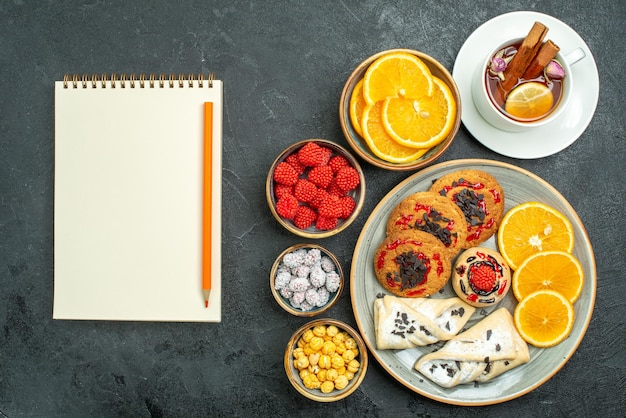 Bovenaanzicht lekkere koekjes met gebak, sinaasappelschijfjes, noten en kopje thee op de donkere achtergrond, theenootkoekje, zoete cake