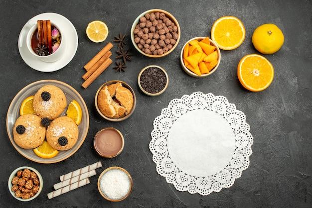 Bovenaanzicht lekkere koekjes met kopje thee en stukjes sinaasappel op donkere bureau taart taart suiker dessert biscuit thee