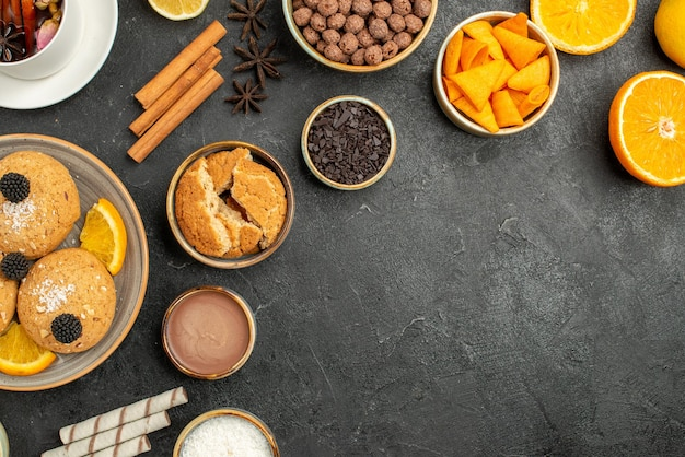 Bovenaanzicht lekkere koekjes met kopje thee en stukjes sinaasappel op een donkere ondergrond cake taart suiker dessert biscuit thee