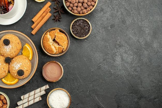 Bovenaanzicht lekkere koekjes met kopje thee op donkere oppervlakte cake taart suiker dessert biscuit thee koekje