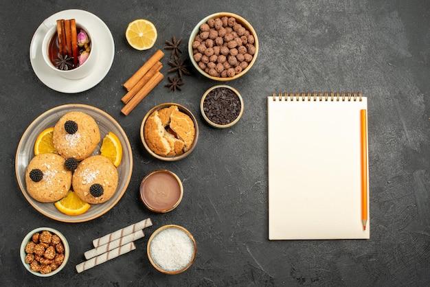 Bovenaanzicht lekkere koekjes met kopje thee op donkergrijs oppervlak cake taart dessert biscuit thee cookie