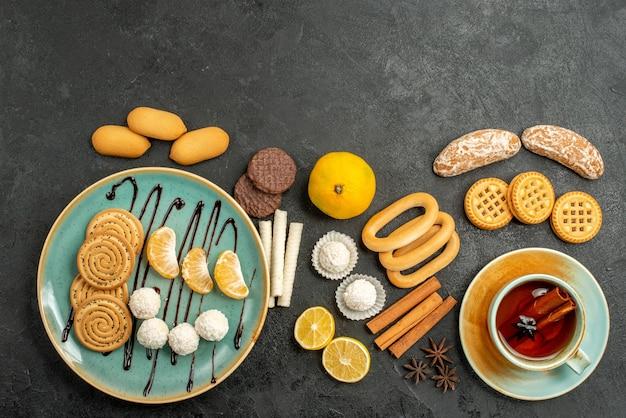 Bovenaanzicht lekkere koekjes met kopje thee op grijze achtergrond