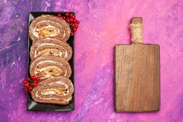 Bovenaanzicht lekkere koekjesbroodjes met fruit op roze achtergrond