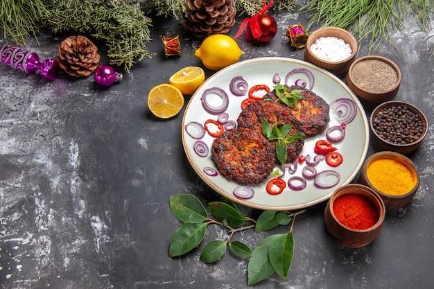 Bovenaanzicht lekkere koteletten met uienringen op de grijze achtergrondfoto van de schotelvleesmaaltijd
