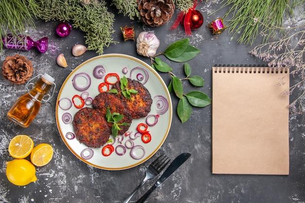 Bovenaanzicht lekkere koteletten met uienringen op de grijze achtergrondfoto van de vleesgerechtmaaltijd