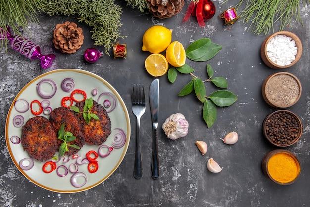 Bovenaanzicht lekkere koteletten met uienringen op de grijze keuken van het achtergrondschotelvlees