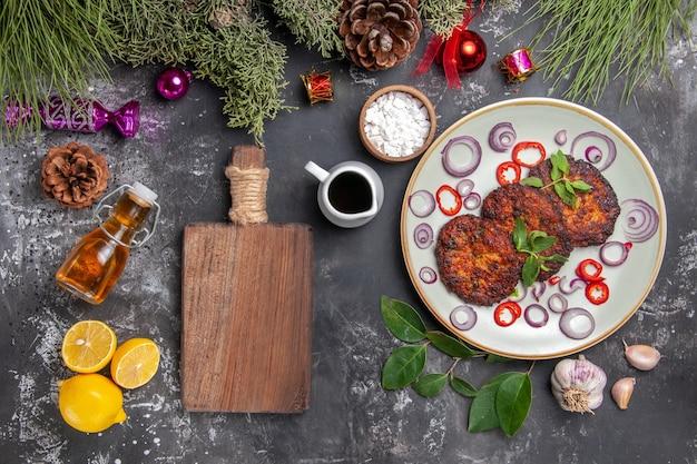 Bovenaanzicht lekkere koteletten met uienringen op het grijze vlees van de de maaltijdfoto van de achtergrondschotel