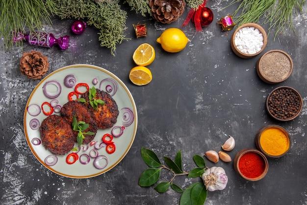 Bovenaanzicht lekkere koteletten met uienringen op het grijze vlees van de de schotelfoto van de achtergrondmaaltijd