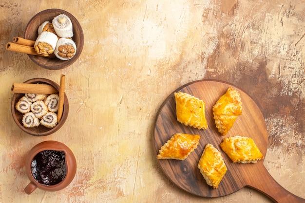 Bovenaanzicht lekkere notencake met confitures op houten achtergrond