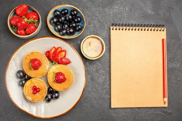 Bovenaanzicht lekkere pannenkoeken, klein gevormd met fruit op de fruitcake van de grijze vloertaart