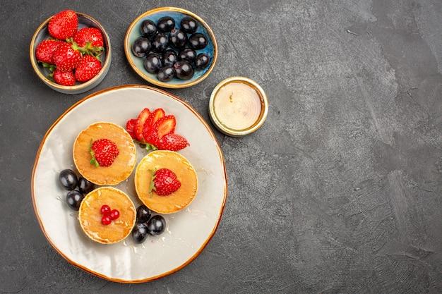 Bovenaanzicht lekkere pannenkoeken, klein gevormd met fruit op het grijs