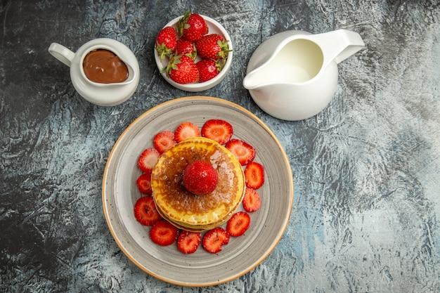 Bovenaanzicht lekkere pannenkoeken met aardbeien en honing op het licht