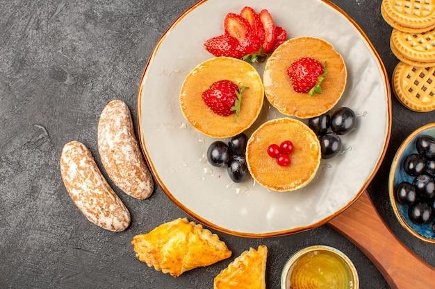 Bovenaanzicht lekkere pannenkoeken met fruit en gebak in het donker