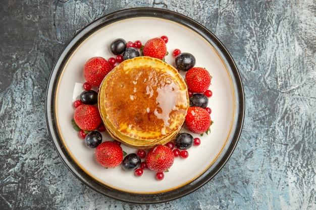 Bovenaanzicht lekkere pannenkoeken met fruit en honing op het licht